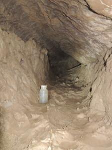 Pohled do odtokového kanálu chodby Užovka. Pro porovnání velikosti na snímku 250ml lahvička.